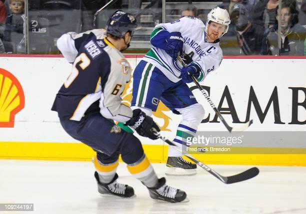 Henrik Sedin of the Vancouver Canucks passes the puck past Shea Weber of the Nashville Predators on February 17 2011 at the Bridgestone Arena in...