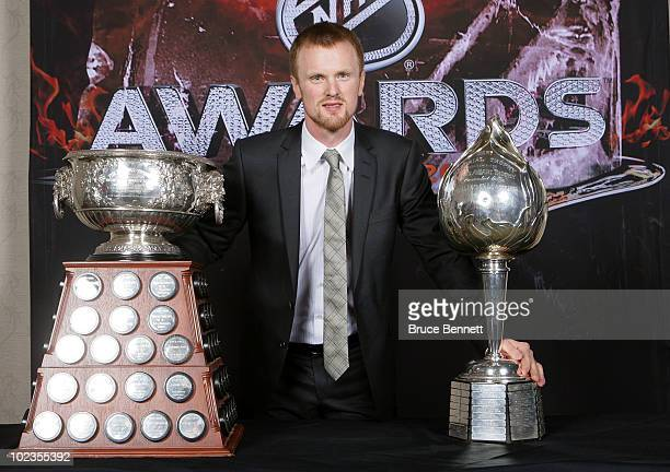 Henrik Sedin of the Vancouver Canucks poses for a portrait with the Hart Memorial Trophy and the Art Ross Trophy during the 2010 NHL Awards at the...