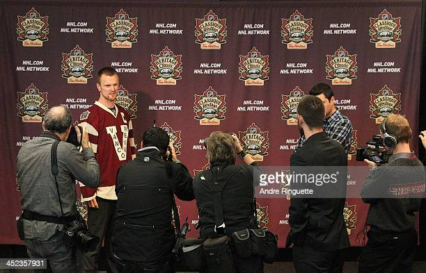 Henrik Sedin of the Vancouver Canucks poses for photographers with his NHL Heritage Classic jersey during the official unveiling at Canadian Tire...