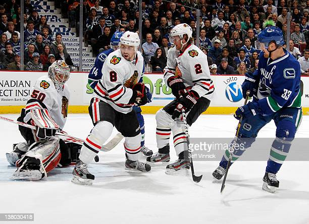 Henrik Sedin of the Vancouver Canucks pursues puck into defenders Duncan Keith Nick Leddy and Corey Crawford of the Chicago Blackhawks during their...