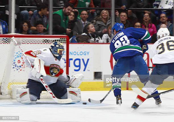 Henrik Sedin of the Vancouver Canucks scores on Roberto Luongo of the Florida Panthers, marking 1000 career points, during their NHL game at Rogers...