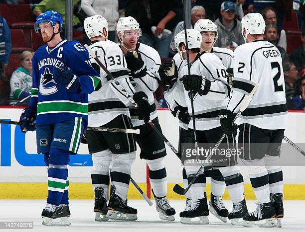 Henrik Sedin of the Vancouver Canucks skates away dejected as Dustin Brown of the Los Angeles Kings is is congratulated by teammates after scoring an...
