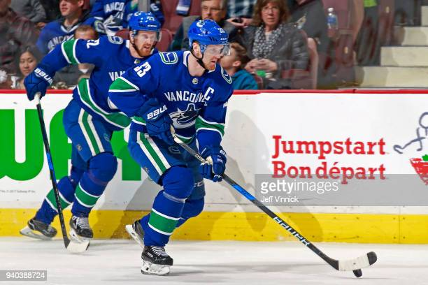 Henrik Sedin of the Vancouver Canucks skates up the ice with teammate Daniel Sedin during their NHL game at Rogers Arena March 31 2018 in Vancouver...