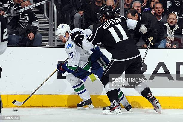 Henrik Sedin of the Vancouver Canucks skates with the puck against Anze Kopitar of the Los Angeles Kings in Game Four of the Western Conference...
