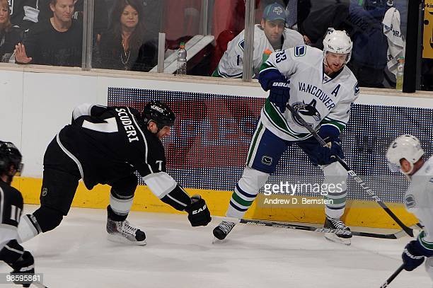 Henrik Sedin of the Vancouver Canucks skates with the puck against Rob Scuderi of the Los Angeles Kings in Game Three of the Western Conference...