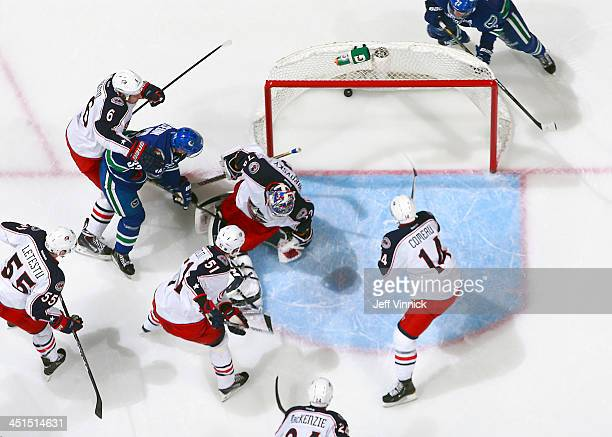 Henrik Sedin of the Vancouver Canucks surrounded by five players scores on Sergei Bobrovsky of the Columbus Blue Jackets during their NHL game at...