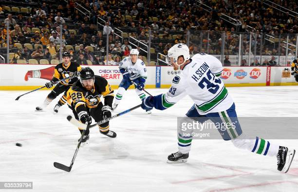Henrik Sedin of the Vancouver Canucks takes a shot against Ian Cole of the Pittsburgh Penguins at PPG Paints Arena on February 14 2017 in Pittsburgh...