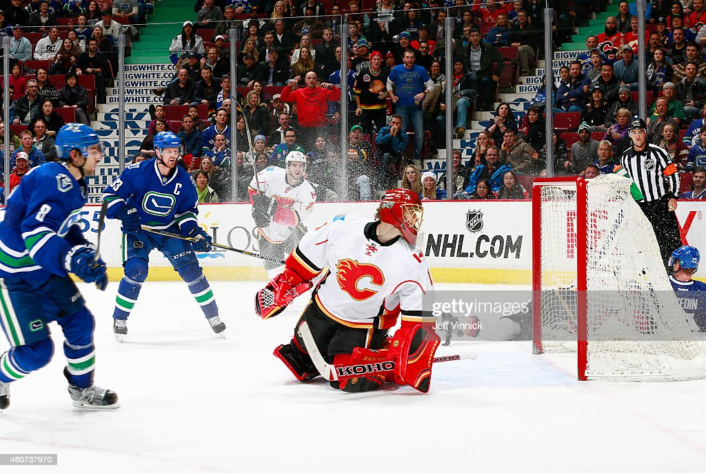 Henrik Sedin #33 of the Vancouver Canucks watches as Christopher Tanev #8 of the Canucks scores in overtime against Jonas Hiller #1 of the Calgary Flames during their NHL game at Rogers Arena December 20, 2014 in Vancouver, British Columbia, Canada. Vancouver won 3-2.