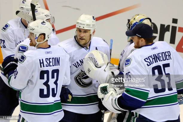 Henrik Sedin Sami Salo and backup goaltender Cory Schneider of the Vancouver Canucks congratulate on another after they defeated the San Jose Sharks...