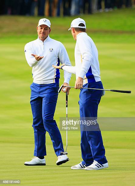 Henrik Stenson of Europe passes the ball to Justin Rose of Europe during the Morning Fourballs of the 2014 Ryder Cup on the PGA Centenary course at...