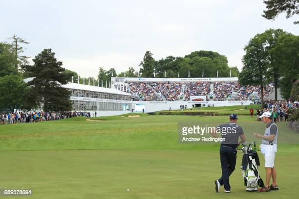 Henrik Stenson of Sweden and caddie Gareth Lord look on from the 18th hole during the final round on day four of the BMW PGA Championship at...