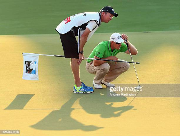 Henrik Stenson of Sweden and his caddie Gareth Lord line up a putt on the 18th green during the second round of the DP World Tour Championship at...