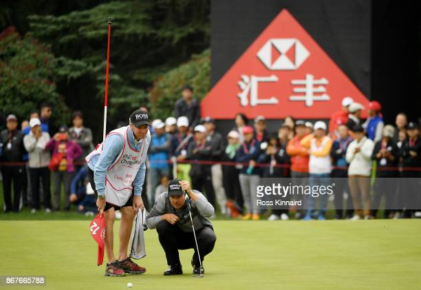 Henrik Stenson of Sweden and his caddie Gareth Lord line up a putt for birdie on the 12th green during the final round of the WGC HSBC Champions at...