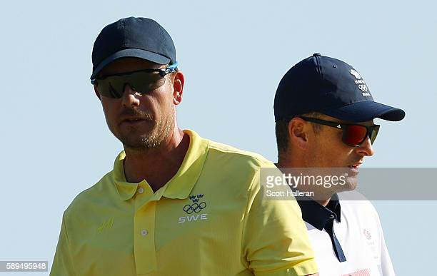 Henrik Stenson of Sweden and Justin Rose of Great Britain stand on the 16th green during the final round of men's golf on Day 9 of the Rio 2016...