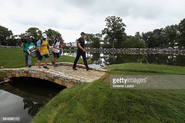 Henrik Stenson of Sweden, caddie Gareth Lord and caddie Craig Connelly cross a bridge on the fourth hole during the final round of the 2016 PGA...