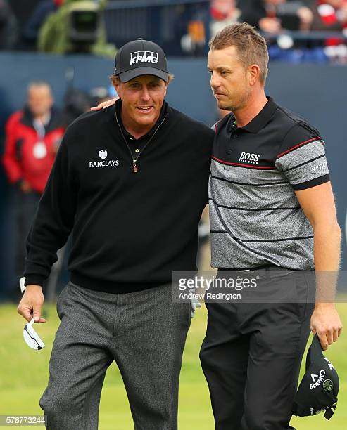 Henrik Stenson of Sweden celebrates victory as he walks off the 18th green with Phil Mickelson of the United States after the final round on day four...