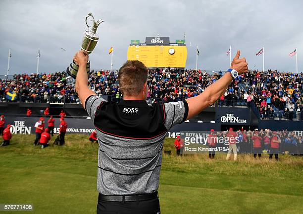 Henrik Stenson of Sweden celebrates with the Claret Jug in front of the grandstand on the 18th hole following his victory during the final round on...