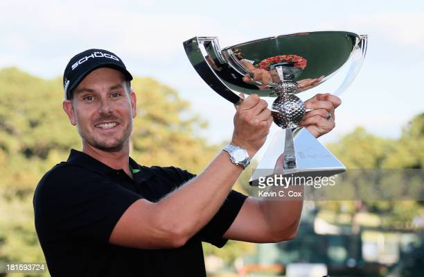 Henrik Stenson of Sweden celebrates with the FedExCup on the 18th green after winning the TOUR Championship by CocaCola and the FedExCup Playoffs at...