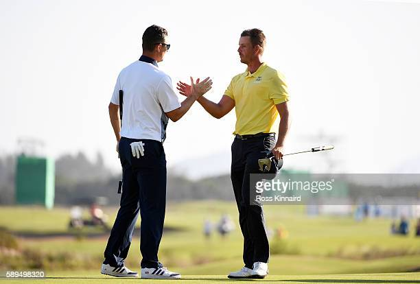 Henrik Stenson of Sweden congratulates Justin Rose of Great Britain as Rose celebrates winning in the final round of men's golf on Day 9 of the Rio...
