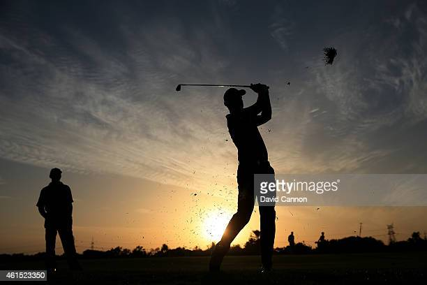 Henrik Stenson of Sweden hits his approach shot on his last hole watched by his coach Pete Cowen during the proam for the Abu Dhabi HSBC Golf...