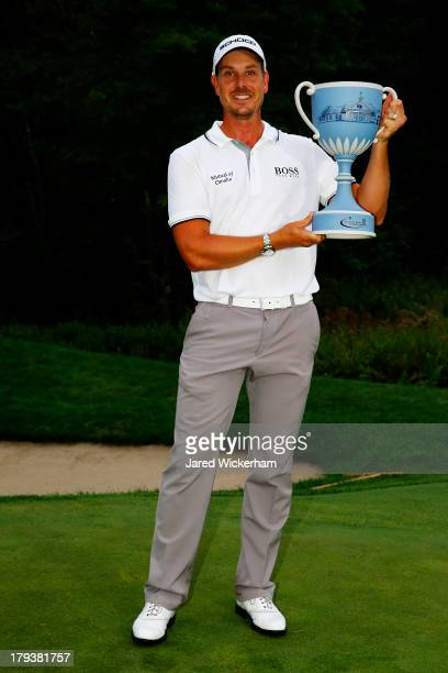 Henrik Stenson of Sweden is presented with the winner's trophy after winning the Deutsche Bank Championship at TPC Boston on September 2, 2013 in...