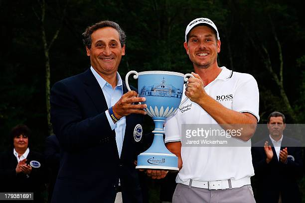 Henrik Stenson of Sweden is presented with the winner's trophy by CEO of Deutsche Bank North America Jacques Brand after winning the Deutsche Bank...