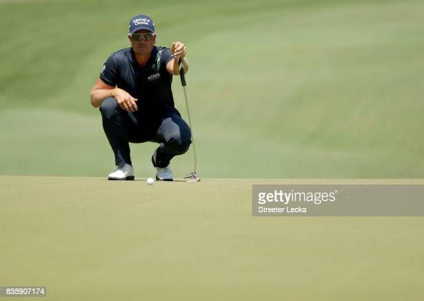 Henrik Stenson of Sweden lines up a putt on the first hole during the final round of the Wyndham Championship at Sedgefield Country Club on August...