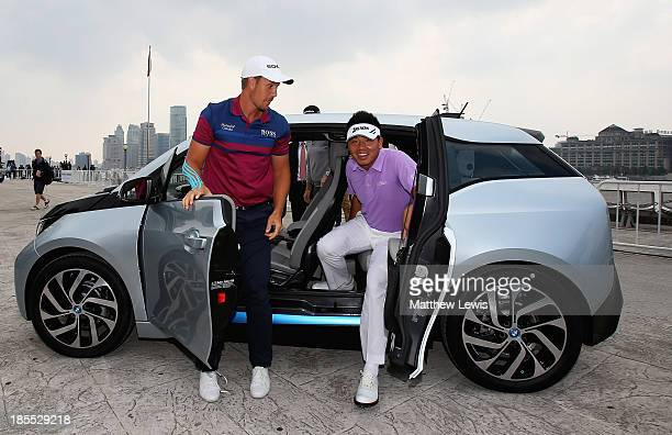 Henrik Stenson of Sweden looks on with Wu Ashun of China as they get of a BMW i3 during the 'Nearest the Pin' competition at Binjang Avenue on...