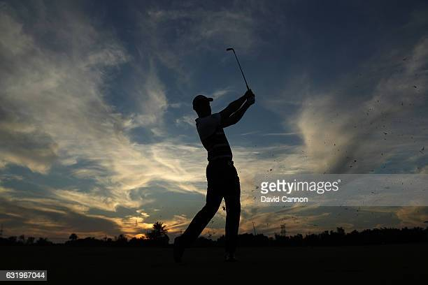 Henrik Stenson of Sweden plays a shot against the setting sun on his final hole during the proam for the 2017 Abu Dhabi HSBC Golf Championship at Abu...