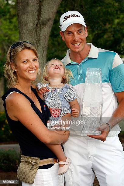 Henrik Stenson of Sweden poses with his wife Emma and daughter Lisa while holding the trophy after his four stroke victory during the final round of...
