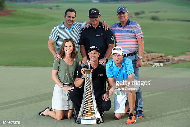 Henrik Stenson of Sweden poses with the Race to Dubai trophy caddie Gareth Lord Coach Pete Cowen and support staff during day four of the DP World...