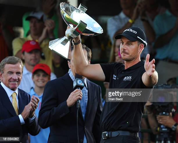 Henrik Stenson of Sweden presents the FedEx Cup to the gallery on the 18th green after winning the TOUR Championship and the FedEx Cup playoffs by...