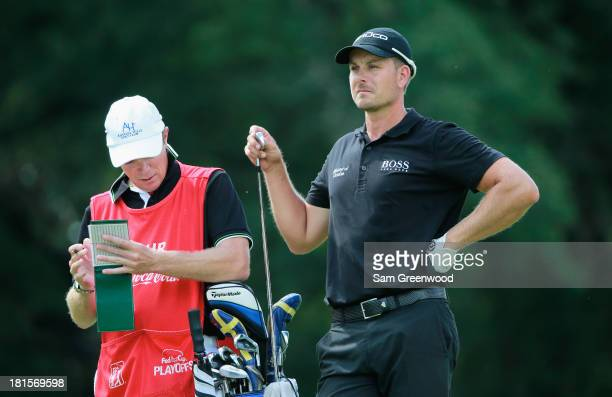 Henrik Stenson of Sweden pulls a club on the fifth hole as his caddie Gareth Lord looks on during the final round of the TOUR Championship by...