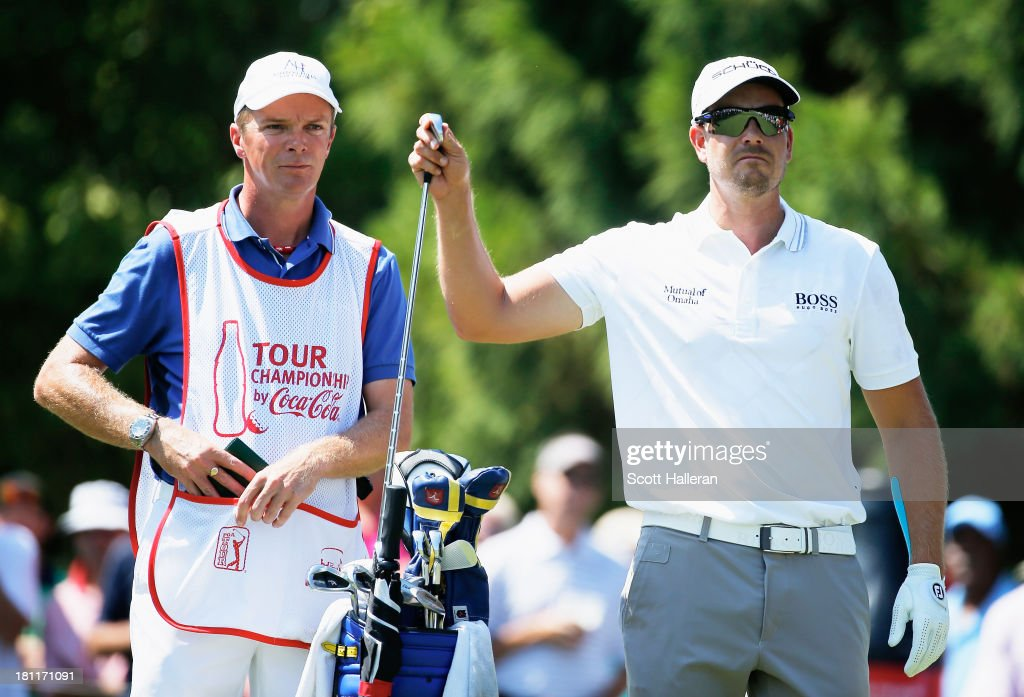 Henrik Stenson of Sweden pulls a club on the second tee alongside his caddie Gareth Lord during the first round of the TOUR Championship by Coca-Cola at East Lake Golf Club on September 19, 2013 in Atlanta, Georgia.