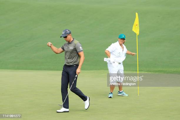 Henrik Stenson of Sweden reacts on the second green with caddie Fanny Sunesson during the first round of the Masters at Augusta National Golf Club on...