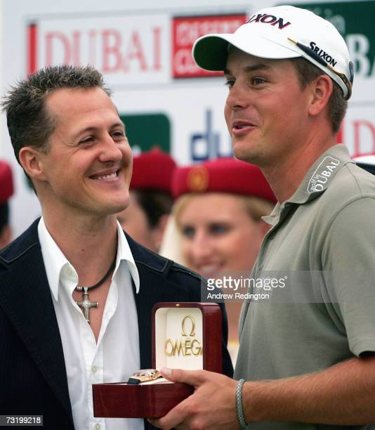 Henrik Stenson of Sweden receives a watch from motor racing legend Michael Schumacher at the prizegiving for the Dubai Desert Classic on the Majilis...