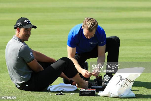 Henrik Stenson of Sweden receives treatment from physiotherapist Nigel Tilley on the second hole during round three of the Abu Dhabi HSBC Golf...