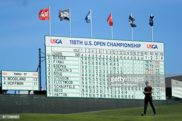 Henrik Stenson of Sweden walks in front of a leaderboard on the 14th green during the final round of the 2018 US Open at Shinnecock Hills Golf Club...