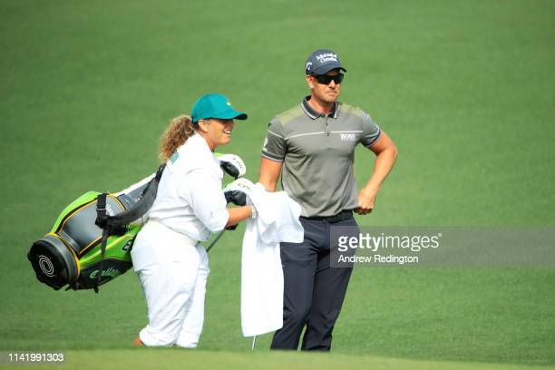 Henrik Stenson of Sweden walks to the second green with caddie Fanny Sunesson during the first round of the Masters at Augusta National Golf Club on...