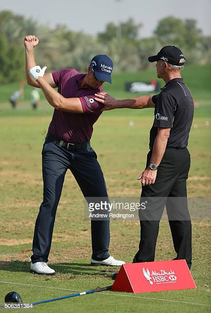 Henrik Stenson of Sweden works with coach Pete Cowen on the practice range prior to his third round of the Abu Dhabi HSBC Golf Championship at the...