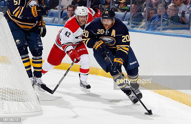 Henrik Tallinder of the Buffalo Sabres skates with the puck against Brett Sutter of the Carolina Hurricanes in a preseason game at First Niagara...