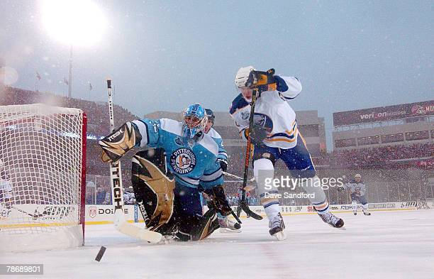 Henrik Tallinder of the Buffalo Sabres tries to get past goaltender Ty Conklin of the Pittsburgh Penguins during the NHL Winter Classic at the Ralph...