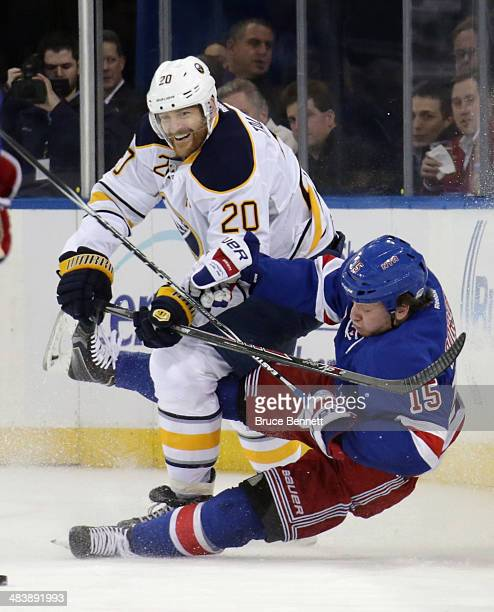 Henrik Tallinder of the Buffalo Sabres trips up Derek Dorsett of the New York Rangers during the first period at Madison Square Garden on April 10...