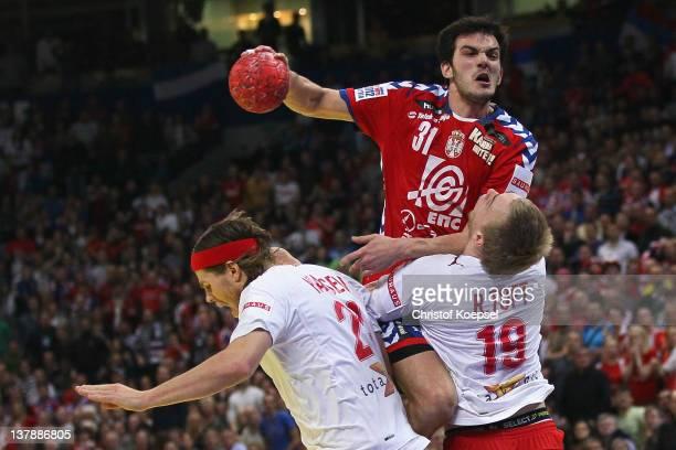Henrik Toft Hansen and Rene Toft Hansen of Denmark defend against Petar Nenadic of Serbia during the Men's European Handball Championship final match...
