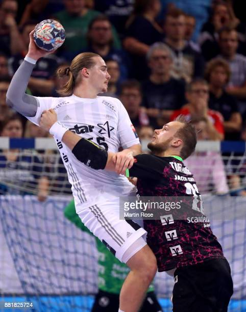 Henrik Toft Hansen of Flensburg Handewitt challenges Lukas Nilsson of Kiel for the ball during the Velux EHF Champions League match between SG...