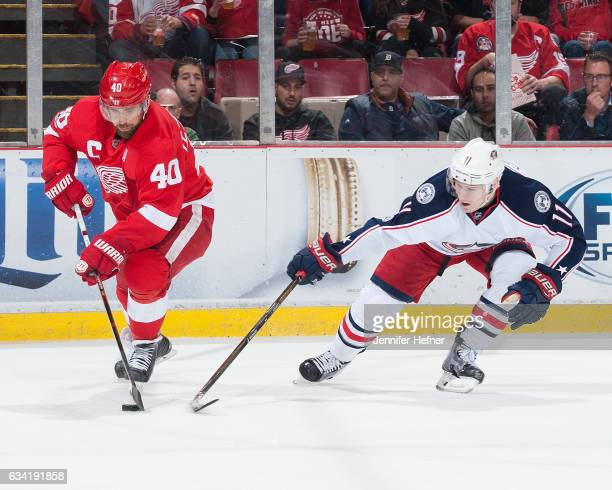 Henrik Zetterberg of the Detroit Red Wings and Matt Calvert of the Columbus Blue Jackets battle for the puck during an NHL game at Joe Louis Arena on...