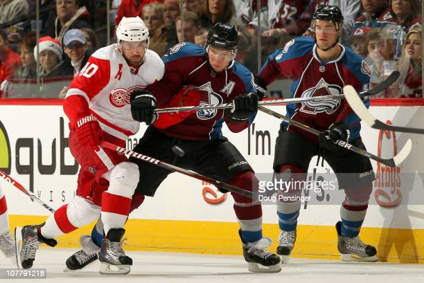 Henrik Zetterberg of the Detroit Red Wings and Paul Stastny of the Colorado Avalanche battle for the puck as TJ Galiardi of the Avalanche follows the...