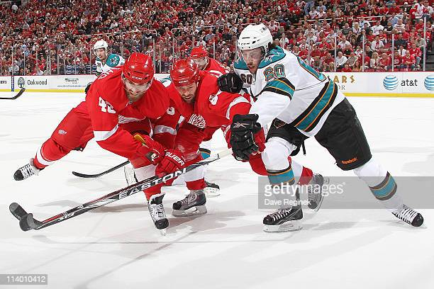 Henrik Zetterberg of the Detroit Red Wings and teammate Tomas Holmstrom reach after puck alongside Jason Demers of the San Jose Sharks during Game...