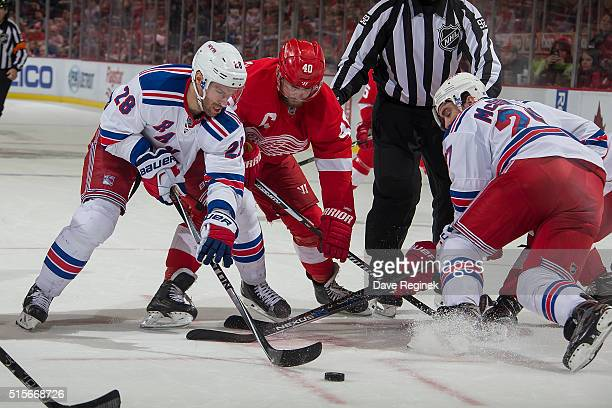 Henrik Zetterberg of the Detroit Red Wings battles for the puck with Dominic Moore and Ryan McDonagh of the New York Rangers during an NHL game at...