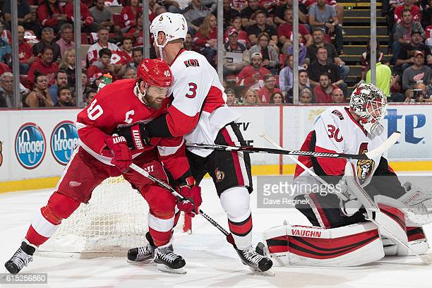 Henrik Zetterberg of the Detroit Red Wings battles in front of the net with Marc Methot of the Ottawa Senators during an NHL game at Joe Louis Arena...